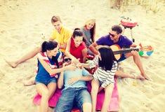 Gruppo di amici con la chitarra divertendosi sulla spiaggia Fotografia Stock Libera da Diritti