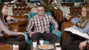 Gruppo di amici dei giovani che si incontrano in un caffè, accogliendosi, stringente le mani video d archivio