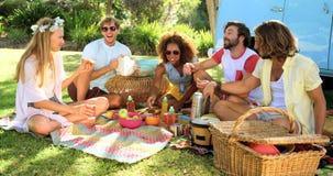 Gruppo di amici dei pantaloni a vita bassa che ridono e che hanno un picnic video d archivio