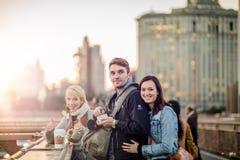 Gruppo di amici dei turisti sul ponte di Brooklyn durante il tramonto Immagine Stock