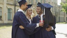 Gruppo di amici dell'istituto universitario in regalia accademica che abbraccia insieme, giorno di laurea stock footage