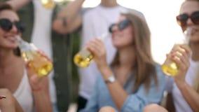Gruppo di amici divertendosi che gode di una bevanda e che si rilassa sulla spiaggia al tramonto al rallentatore Giovani e donne archivi video