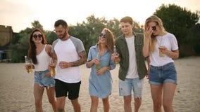 Gruppo di amici divertendosi che gode di una bevanda e che si rilassa sulla spiaggia al tramonto al rallentatore Giovani e donne stock footage