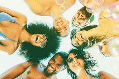 Gruppo di amici divertendosi esame sorridente giù la macchina fotografica giovani in abbigliamento da spiaggia che godono facendo fotografia stock