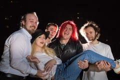 Gruppo di amici divertendosi insieme all'aperto in una notte ed in una luce dietro fotografie stock libere da diritti