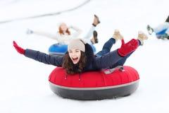 Gruppo di amici felici che fanno scorrere giù sui tubi della neve Fotografie Stock Libere da Diritti