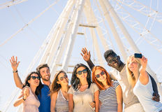 Gruppo di amici felici multirazziali che prendono selfie alla ruota di ferris fotografia stock libera da diritti