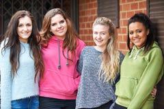 Gruppo di amici femminili adolescenti nell'ambiente urbano fotografia stock