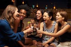 Gruppo di amici femminili che godono della notte fuori al tetto Antivari immagini stock libere da diritti