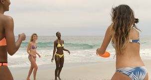Gruppo di amici femminili razza mista che giocano il disco di volo sulla spiaggia 4k video d archivio
