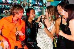 Gruppo di amici in locale notturno Fotografia Stock