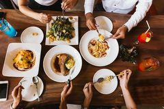 Gruppo di amici maschii e femminili cenando e mangiando bistecca ed insalata e spaghetti insieme nel ristorante - vista superiore immagine stock