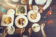 Gruppo di amici maschii e femminili cenando e mangiando bistecca ed insalata e spaghetti insieme nel ristorante - vista superiore fotografia stock