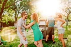 Gruppo di amici multi-etnici che mangiano le birre e che cucinano sul barbecue del giardino Stile di vita, concetto di svago immagini stock