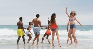 Gruppo di amici razza mista che ballano insieme sulla spiaggia 4k video d archivio