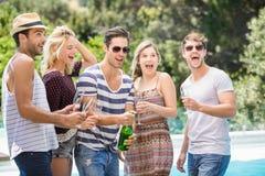 Gruppo di amici schioccando una bottiglia del champagne fotografie stock