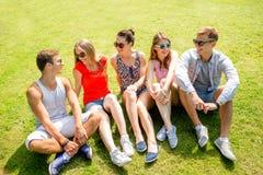 Gruppo di amici sorridenti all'aperto che si siedono nel parco Immagine Stock Libera da Diritti