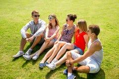 Gruppo di amici sorridenti all'aperto che si siedono nel parco Fotografia Stock Libera da Diritti
