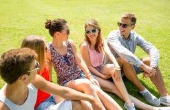 Gruppo di amici sorridenti all'aperto che si siedono nel parco Immagini Stock