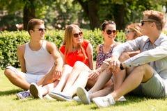 Gruppo di amici sorridenti all'aperto che si siedono sull'erba Fotografie Stock