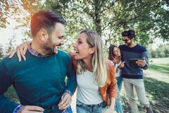 Gruppo di amici sorridenti all'aperto in parco Fotografia Stock Libera da Diritti