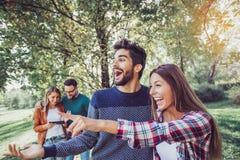 Gruppo di amici sorridenti all'aperto in parco Fotografie Stock Libere da Diritti