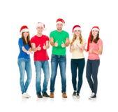 Gruppo di amici sorridenti in cappelli di Natale Immagini Stock