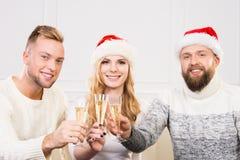 Gruppo di amici sorridenti in cappelli di Natale che celebrano Immagine Stock Libera da Diritti