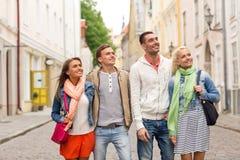 Gruppo di amici sorridenti che camminano nella città Fotografie Stock Libere da Diritti