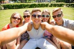 Gruppo di amici sorridenti che fanno selfie in parco