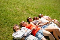 Gruppo di amici sorridenti che si trovano sull'erba all'aperto Immagini Stock Libere da Diritti