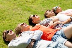 Gruppo di amici sorridenti che si trovano sull'erba all'aperto Fotografie Stock
