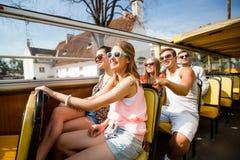 Gruppo di amici sorridenti che viaggiano in bus di giro fotografia stock