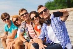 Gruppo di amici sorridenti con lo smartphone all'aperto Fotografia Stock