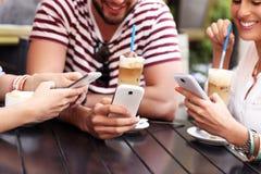 Gruppo di amici in un caffè facendo uso degli smartphones Immagini Stock