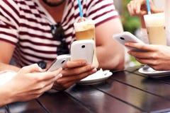 Gruppo di amici in un caffè facendo uso degli smartphones Immagini Stock Libere da Diritti