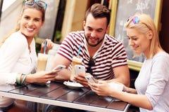 Gruppo di amici in un caffè facendo uso degli smartphones Fotografia Stock