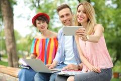 Gruppo di amici in vestiti alla moda che prendono selfie all'aperto Immagine Stock