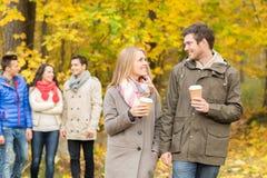 Gruppo di amico sorridente con le tazze di caffè in parco Fotografie Stock Libere da Diritti
