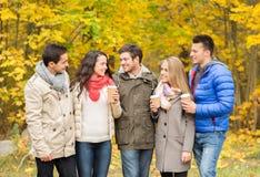 Gruppo di amico sorridente con le tazze di caffè in parco Fotografia Stock Libera da Diritti