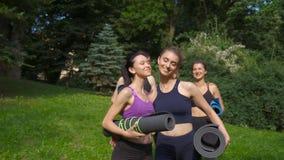 Gruppo di andare femminile sorridente cinque attivi per l'allenamento, tenente le stuoie di yoga nella mattina di estate al parco archivi video