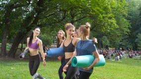 Gruppo di andare femminile sorridente cinque attivi per l'allenamento, tenente le stuoie di yoga nella mattina di estate al parco stock footage