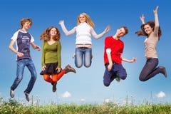 Gruppo di anni dell'adolescenza che saltano nel cielo blu sopra l'erba verde Fotografia Stock