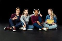 gruppo di anni dell'adolescenza con i dispositivi digitali che si siedono sul pavimento fotografia stock