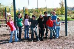 Gruppo di anni dell'adolescenza su swingset Fotografia Stock Libera da Diritti