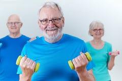 Gruppo di anziani nella classe di forma fisica facendo uso dei pesi fotografie stock libere da diritti
