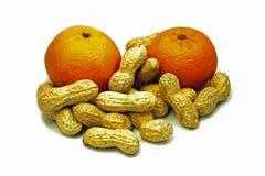 Gruppo di arachidi intorno due mandarini Isolato su priorità bassa bianca immagini stock libere da diritti