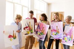 Gruppo di artisti con le immagini alla scuola di arte fotografie stock