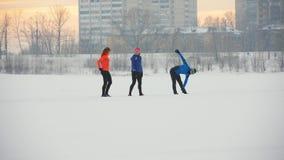 Gruppo di atleti che si scaldano e che allungano prima dell'esercizio nella foresta di inverno video d archivio