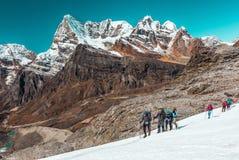 Gruppo di atleti del ghiacciaio differente dell'incrocio di età in alte montagne Fotografia Stock Libera da Diritti